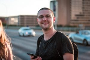 Best looking gamedev Garrett Mickley, a white man with short hair standing on a bridge with cars in the background.